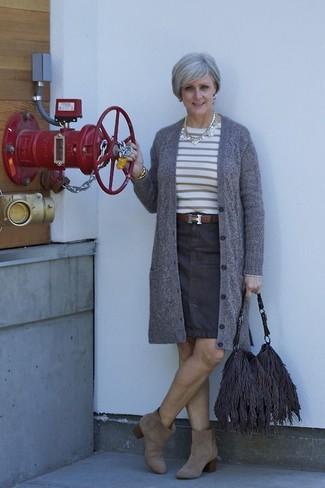 Лук из серого кардигана и темно-синей джинсовой юбки-карандаш поможет выглядеть аккуратно, но при этом выразить твой индивидуальный стиль. Очень уместно здесь смотрятся коричневые замшевые ботильоны.