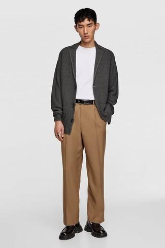 Мода для 20-летних мужчин: Темно-серый кардиган в сочетании со светло-коричневыми классическими брюками — воплощение строгого делового стиля. Черные кожаные лоферы станут отличным дополнением к твоему луку.