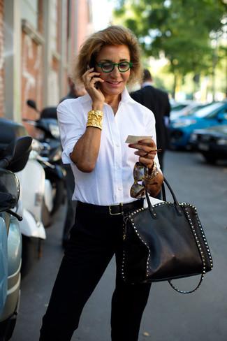 Как и с чем носить: белая классическая рубашка, черные брюки-галифе, черная кожаная большая сумка с шипами, черный кожаный ремень