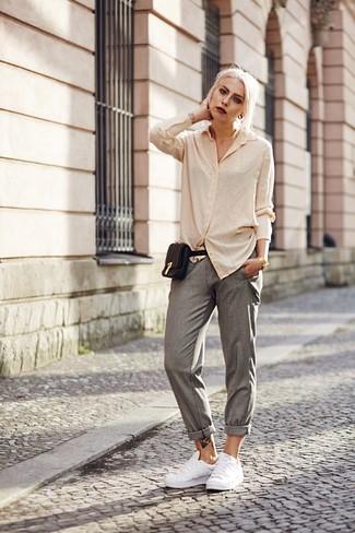 Как и с чем носить: бежевая классическая рубашка, серые брюки-галифе, белые кожаные низкие кеды, черная кожаная поясная сумка