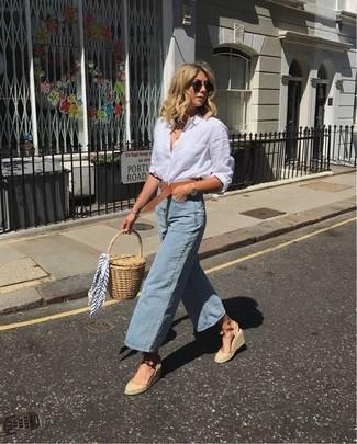 Как и с чем носить: белая льняная классическая рубашка, голубые джинсовые брюки-кюлоты, бежевые босоножки на танкетке из плотной ткани, светло-коричневый соломенный клатч