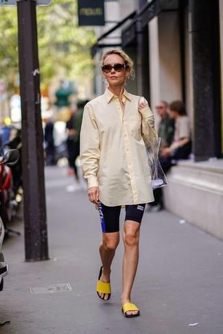 Модный лук: желтая классическая рубашка, черные велосипедки с принтом, желтые резиновые сандалии на плоской подошве, прозрачная резиновая большая сумка
