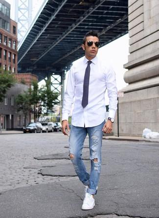 белая классическая рубашка в паре с синими рваными джинсами легко вписывается в разные дресс-коды. Любители экспериментировать могут завершить образ белыми низкими кедами.