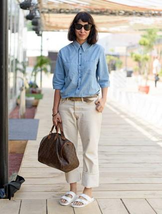 Как и с чем носить: голубая классическая рубашка из шамбре, бежевые джинсы, белые кожаные сандалии на плоской подошве, темно-коричневая кожаная спортивная сумка с принтом