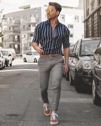 Как и с чем носить: темно-сине-белая классическая рубашка в вертикальную полоску, серые зауженные джинсы, табачные замшевые низкие кеды, светло-коричневый кожаный ремень