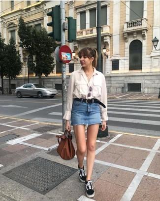 Как и с чем носить: бежевая классическая рубашка, синяя джинсовая мини-юбка, черно-белые низкие кеды из плотной ткани, коричневая кожаная большая сумка