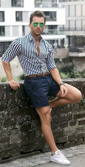 Как и с чем носить: бело-темно-синяя классическая рубашка в вертикальную полоску, темно-синие шорты, белые низкие кеды, коричневый кожаный ремень