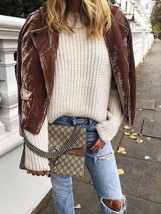 Как и с чем носить: коричневая замшевая косуха, бежевый вязаный свободный свитер, синие рваные джинсы, коричневая кожаная сумка через плечо с принтом