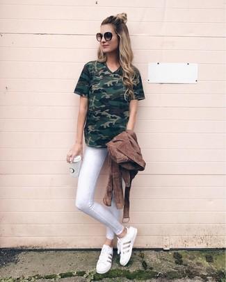 Как и с чем носить: коричневая замшевая косуха, темно-зеленая футболка с v-образным вырезом с камуфляжным принтом, белые джинсы скинни, белые кожаные низкие кеды