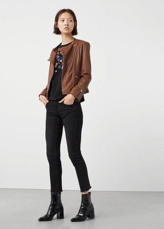 Как и с чем носить: коричневая кожаная косуха, черный свитер с круглым вырезом с цветочным принтом, черные джинсы скинни, черные кожаные ботильоны