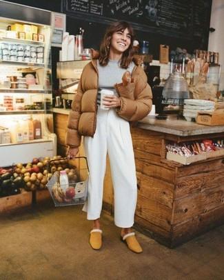 Как и с чем носить: коричневая куртка-пуховик, серый свитер с круглым вырезом, белые широкие брюки, светло-коричневые замшевые сабо