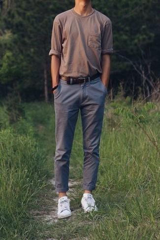 Мода для 30-летних мужчин: Поклонникам расслабленного стиля придется по вкусу сочетание коричневой футболки с длинным рукавом и серых брюк чинос. Пара белых низких кед свяжет ансамбль воедино.