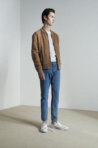 Коричневый замшевый бомбер: с чем носить и как сочетать мужчине: Коричневый замшевый бомбер выглядит прекрасно в тандеме с синими джинсами. Вкупе с этим луком органично выглядят белые низкие кеды из плотной ткани.