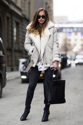Как и с чем носить: серая короткая дубленка, бело-черная блузка с длинным рукавом с принтом, черные джинсы скинни, черные кожаные ботильоны