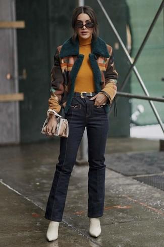 Как и с чем носить: разноцветная короткая дубленка, горчичная водолазка, темно-синие джинсы-клеш, белые кожаные ботильоны