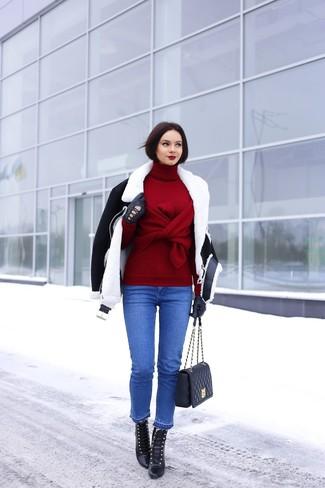 Черно-белая короткая дубленка и синие джинсы — беспроигрышный вариант непринужденного повседневного лука. Черные кожаные ботильоны на шнуровке добавят образу изысканности.