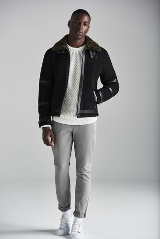 Как и с чем носить: черная короткая дубленка, белый вязаный свитер, серые брюки чинос, белые кожаные низкие кеды