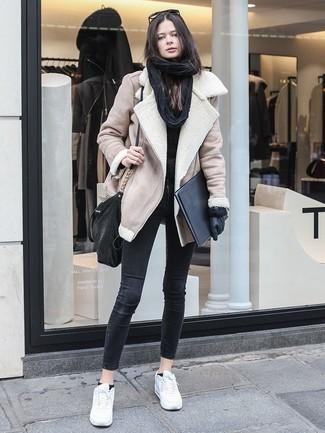 Как и с чем носить: бежевая короткая дубленка, черный свитер с круглым вырезом, черные джинсы скинни, белые кожаные низкие кеды