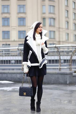 Как и с чем носить: черно-белая короткая дубленка, белый свитер с круглым вырезом, черная короткая юбка-солнце, черные замшевые ботинки на шнуровке