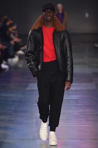 Как и с чем носить: черная короткая дубленка, красный свитер с круглым вырезом, черные спортивные штаны, белые кожаные низкие кеды