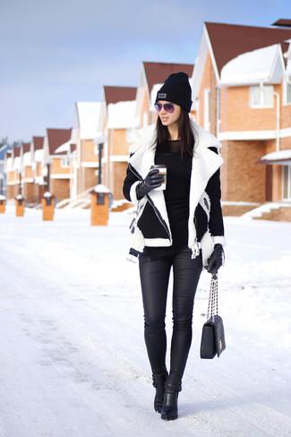 Черно-белая короткая дубленка и черные кожаные джинсы скинни — великолепный вариант для вечера в компании друзей. Сделать образ изысканнее помогут черные кожаные ботильоны.