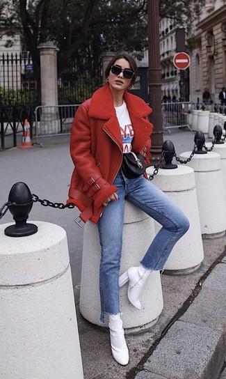 Как и с чем носить: красная короткая дубленка, бело-красная футболка с круглым вырезом с принтом, синие джинсы, белые ботильоны на резинке