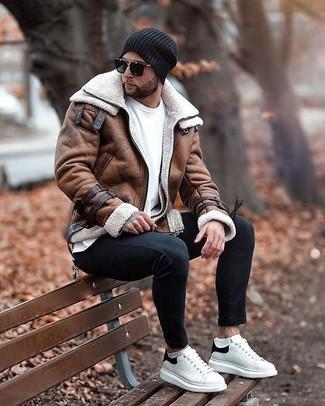 Мода для 20-летних мужчин: Коричневая короткая дубленка в паре с черными зауженными джинсами не прекращает нравиться стильным джентльменам. В тандеме с этим луком наиболее удачно выглядят бело-черные кожаные низкие кеды.