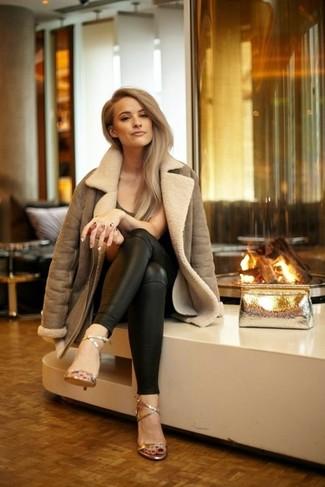 Как и с чем носить: коричневая короткая дубленка, темно-коричневая футболка с круглым вырезом, черные кожаные узкие брюки, золотые кожаные босоножки на каблуке