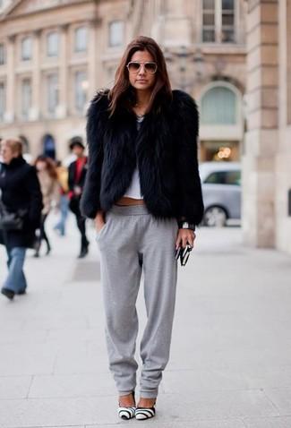 Как и с чем носить: черная короткая шуба, белый укороченный топ, серые спортивные штаны, бело-черные кожаные туфли