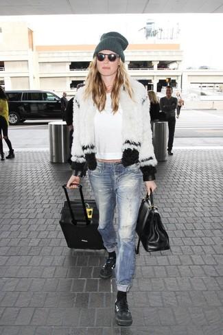 Как и с чем носить: бело-черная короткая шуба, белая футболка с длинным рукавом, синие рваные джинсы, черные кожаные низкие кеды