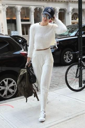 Как и с чем носить: белый пушистый короткий свитер, белые вязаные спортивные штаны, бело-черные кожаные низкие кеды, черная кожаная сумка-саквояж