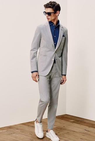 Как и с чем носить: серый костюм из жатого хлопка, темно-синяя джинсовая рубашка, белые кожаные низкие кеды, темно-синий нагрудный платок