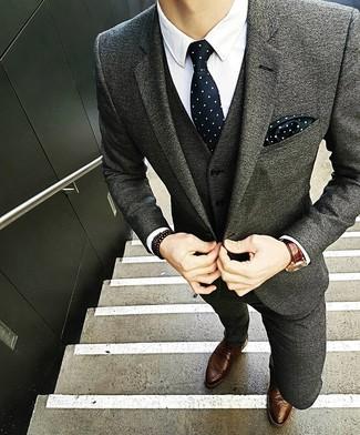 Как и с чем носить: серый шерстяной костюм, белая классическая рубашка, коричневые кожаные броги, черно-белый галстук в горошек