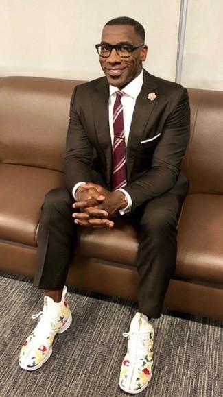 Как и с чем носить: темно-коричневый костюм, белая классическая рубашка, белые высокие кеды с цветочным принтом, красный галстук в вертикальную полоску