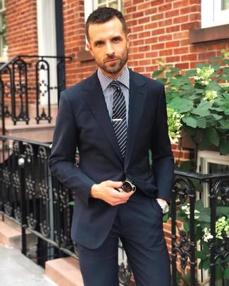 Как и с чем носить: темно-синий костюм, черно-белая классическая рубашка в мелкую клетку, черно-белый галстук в вертикальную полоску, черные солнцезащитные очки