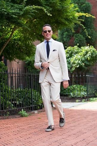 Как и с чем носить: бежевый костюм из жатого хлопка, голубая классическая рубашка, серые лоферы с кисточками из плотной ткани, темно-синий вязаный галстук