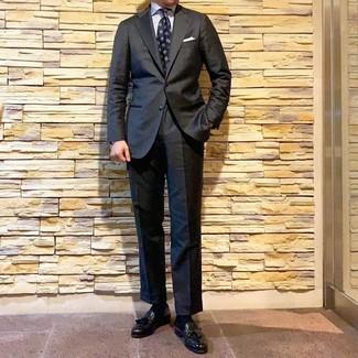 Как и с чем носить: темно-серый костюм, белая классическая рубашка в вертикальную полоску, черные кожаные лоферы с кисточками, темно-синий галстук с принтом
