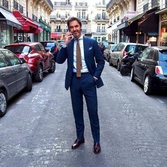 Как и с чем носить: темно-синий костюм в вертикальную полоску, белая классическая рубашка, темно-коричневые кожаные лоферы, коричневый вязаный галстук