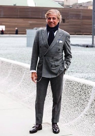 Темно-синий шарф: с чем носить и как сочетать мужчине: Несмотря на свою легкость, сочетание серого костюма и темно-синего шарфа приходится по душе джентльменам, неизбежно покоряя при этом сердца прекрасных дам. Такой лук легко получает свежее прочтение в сочетании с темно-красными кожаными монками с двумя ремешками.