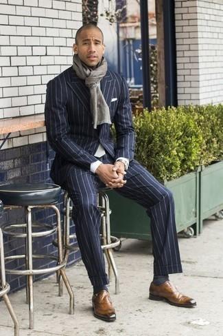Рубашка: с чем носить и как сочетать мужчине: Несмотря на то, что этот ансамбль весьма классический, дуэт рубашки и темно-синего костюма в вертикальную полоску неизменно нравится стильным молодым людям, пленяя при этом сердца прекрасных дам. Теперь почему бы не добавить в повседневный ансамбль толику изысканности с помощью светло-коричневых кожаных монок?
