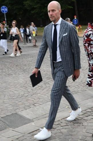 Темно-сине-белый вязаный галстук: с чем носить и как сочетать мужчине: Несмотря на то, что это классический образ, образ из серого костюма в вертикальную полоску и темно-сине-белого вязаного галстука приходится по вкусу джентльменам, непременно покоряя при этом дамские сердца. И почему бы не разнообразить лук с помощью белых низких кед?