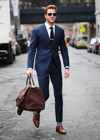 Как и с чем носить: темно-синий костюм, белая классическая рубашка, коричневые кожаные оксфорды, коричневая дорожная сумка из плотной ткани