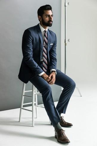 Как и с чем носить: темно-синий костюм, белая классическая рубашка, темно-коричневые кожаные оксфорды, серый галстук в вертикальную полоску