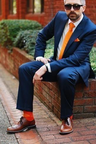 Оранжевые носки: с чем носить и как сочетать мужчине: Если ты ценишь комфорт и функциональность, тебе понравится сочетание темно-синего костюма и оранжевых носков. Хотел бы сделать ансамбль немного строже? Тогда в качестве обуви к этому образу, стоит обратить внимание на коричневые кожаные оксфорды.
