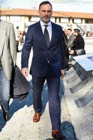 Модные мужские луки 2020 фото в теплую погоду: Темно-синий костюм смотрится стильно в паре с белой классической рубашкой. Если сочетание несочетаемого привлекает тебя не меньше, чем безвременная классика, закончи свой наряд коричневыми кожаными повседневными ботинками.