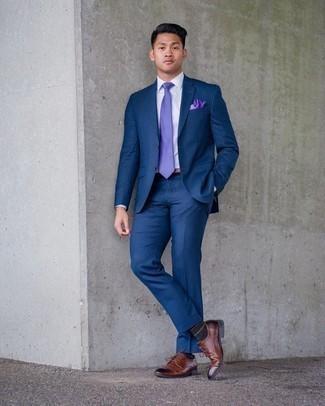 Мода для 20-летних мужчин: Темно-синий костюм в паре с белой классической рубашкой позволит исполнить строгий деловой стиль. Этот лук выигрышно дополнят коричневые кожаные туфли дерби.