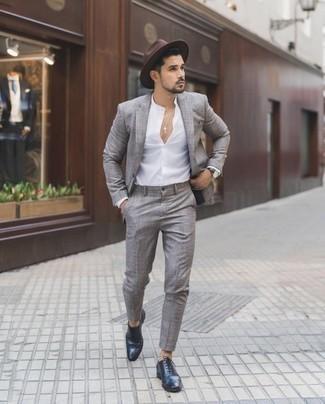 С чем носить темно-коричневую шерстяную шляпу мужчине: Тандем серого костюма в шотландскую клетку и темно-коричневой шерстяной шляпы позволит выглядеть модно, а также подчеркнуть твою индивидуальность. Такой лук получит новое прочтение в паре с темно-синими кожаными брогами.