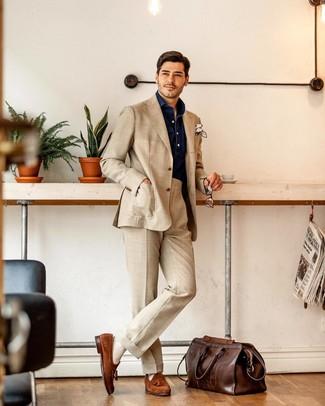Как и с чем носить: бежевый костюм, темно-синяя рубашка с длинным рукавом из шамбре, табачные замшевые лоферы с кисточками, темно-коричневая кожаная дорожная сумка