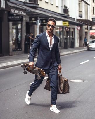 Как и с чем носить: темно-синий костюм, белая рубашка с длинным рукавом, белые кожаные низкие кеды, темно-коричневая кожаная дорожная сумка с принтом