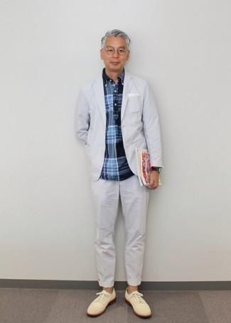 Темно-синяя рубашка с длинным рукавом в шотландскую клетку: с чем носить и как сочетать мужчине: Несмотря на то, что это достаточно выдержанный лук, сочетание темно-синей рубашки с длинным рукавом в шотландскую клетку и белого костюма всегда будет по вкусу стильным молодым людям, неизбежно пленяя при этом сердца представительниц прекрасного пола. Любители экспериментировать могут завершить образ бежевыми замшевыми туфлями дерби, тем самым добавив в него немного утонченности.